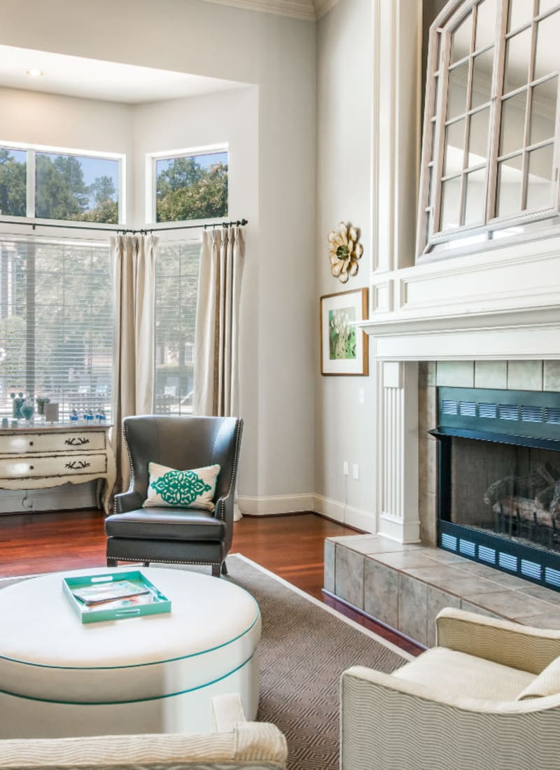 Bright and comfortable sitting area next to fireplace in clubhouse at Marquis at Carmel Commons in Charlotte, North Carolina