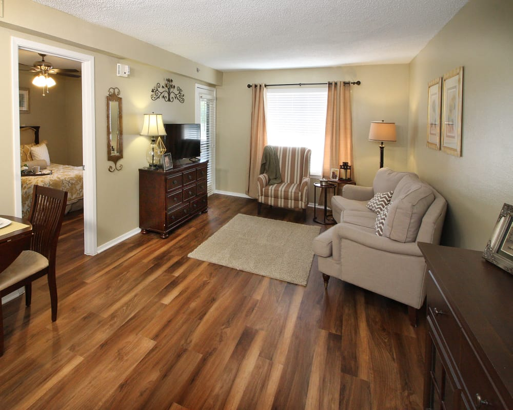 Model living room with hardwood flooring at West Fork Village in Irving, Texas