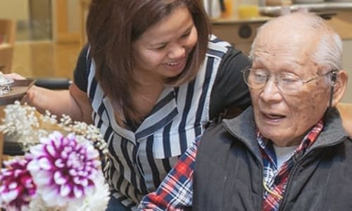 A volunteer with a resident at Nikkei Manor in Seattle, WA