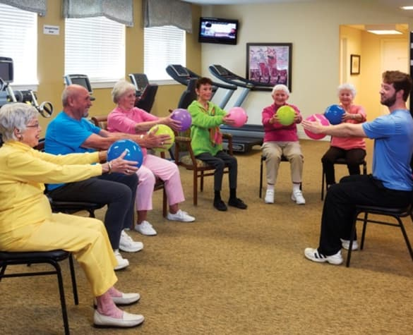 Resident working out with weighted balls at The Enclave at Round Rock Senior Living in Round Rock, Texas