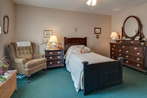 Assisted living apartment bedroom at Victorian Place of Washington Senior Living in Washington, Missouri