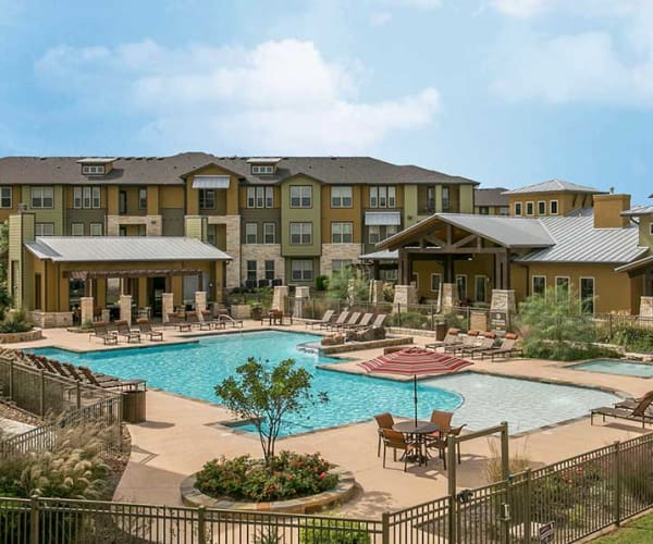 View of Pecos Flats' apartment buildings and pool in San Antonio, Texas