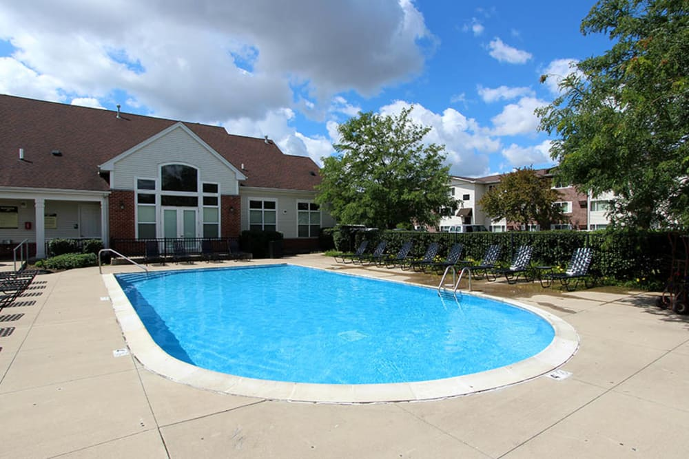 Beautiful resort-style swimming pool with lounge chairs at Riverstone Apartments in Bolingbrook, Illinois