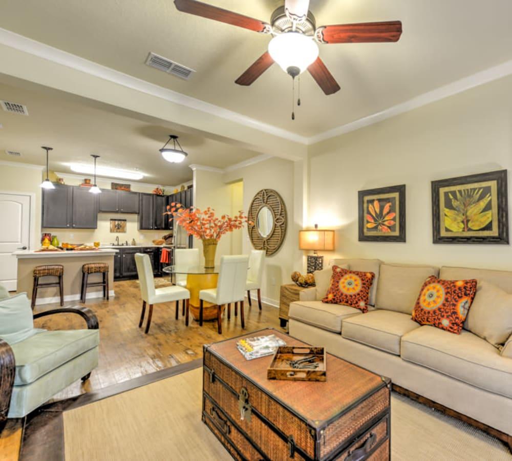 Well-furnished living area with a view of the kitchen in an open-concept model apartment at Hacienda Club in Jacksonville, Florida