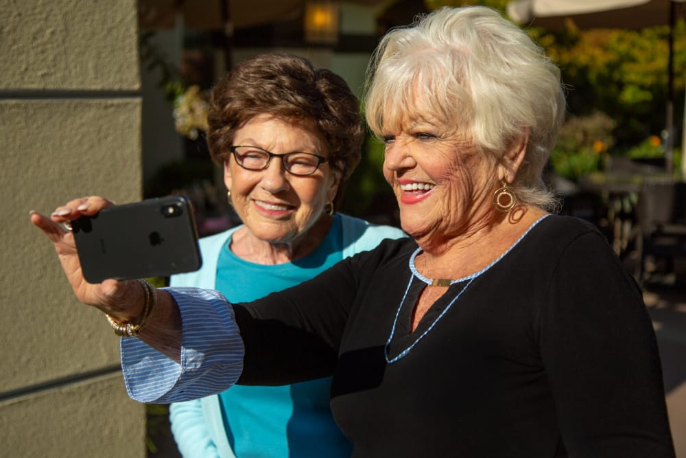 Residents taking a selfie in the courtyard at our senior living community in West Covina
