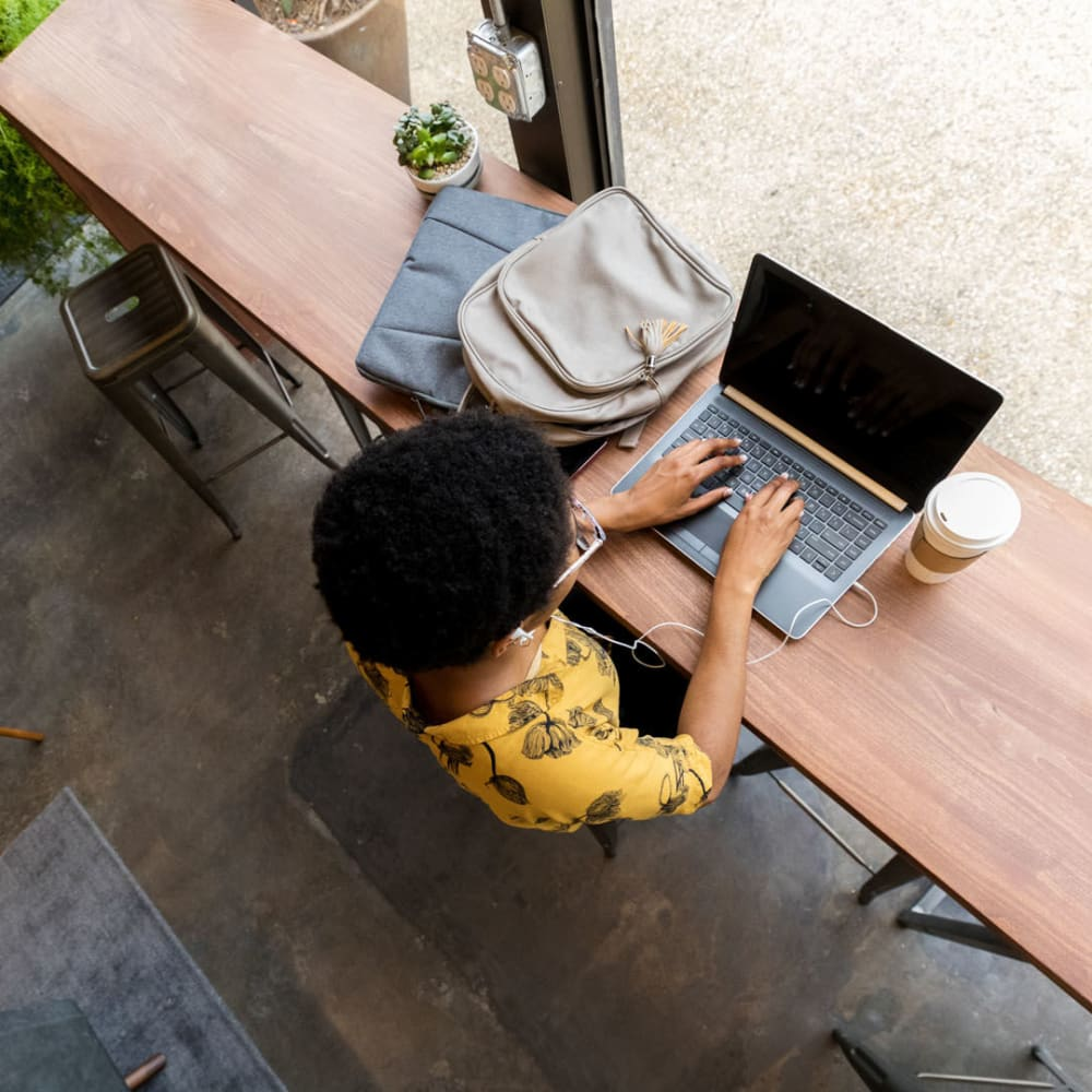 Resident getting some work done on her laptop at a café near Oaks Hackberry Creek in Irving, Texas
