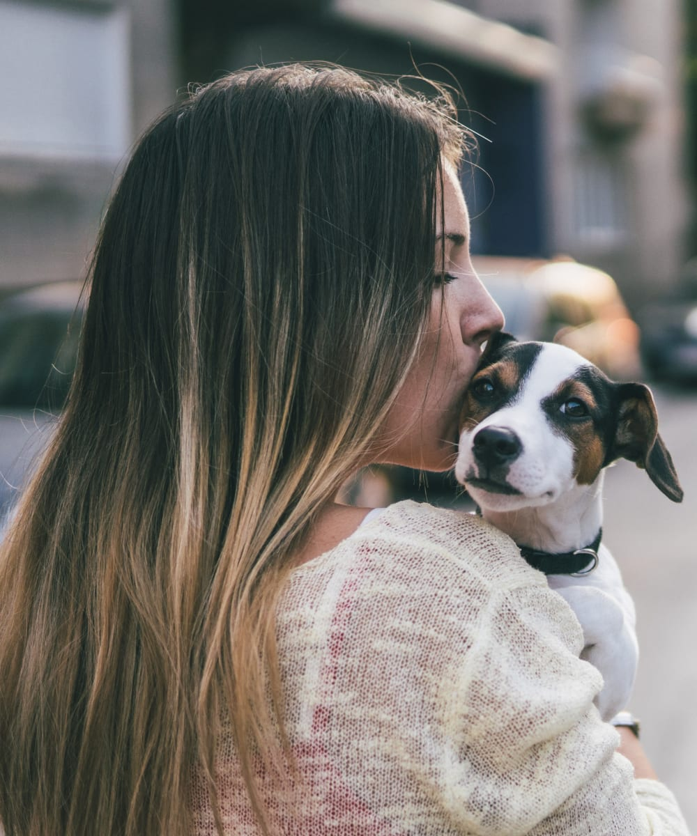 Resident kissing her pup outside their new home at Haven Warner Center in Canoga Park, California