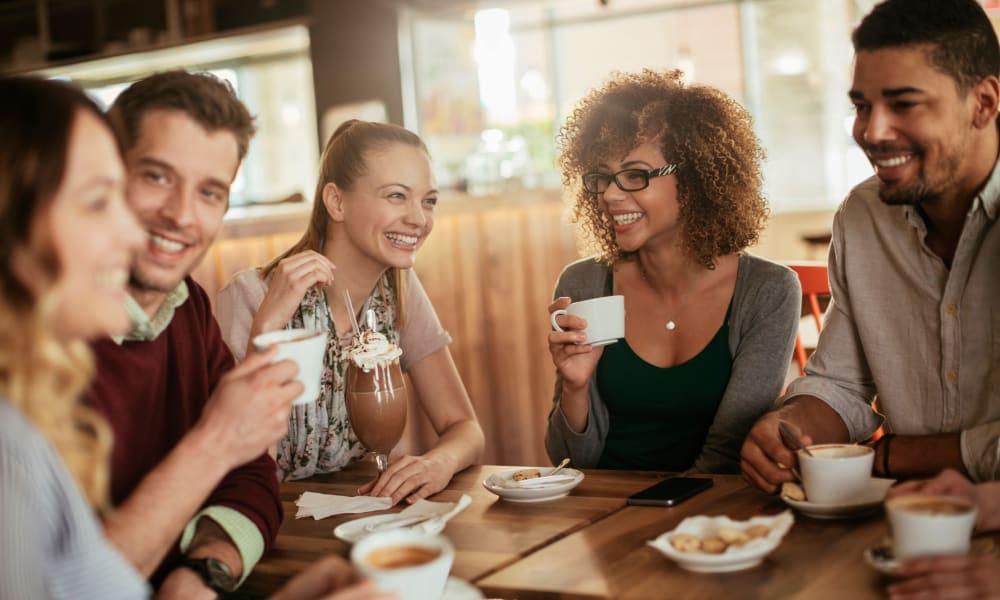 Friends enjoying a local coffee shop near Edgewood Park Apartments in Pontiac, Michigan