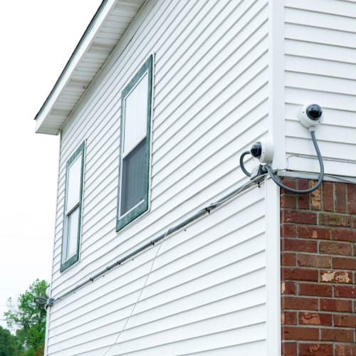 Security camera mounted on a white building with brick at Red Dot Storage in Baker, Louisiana
