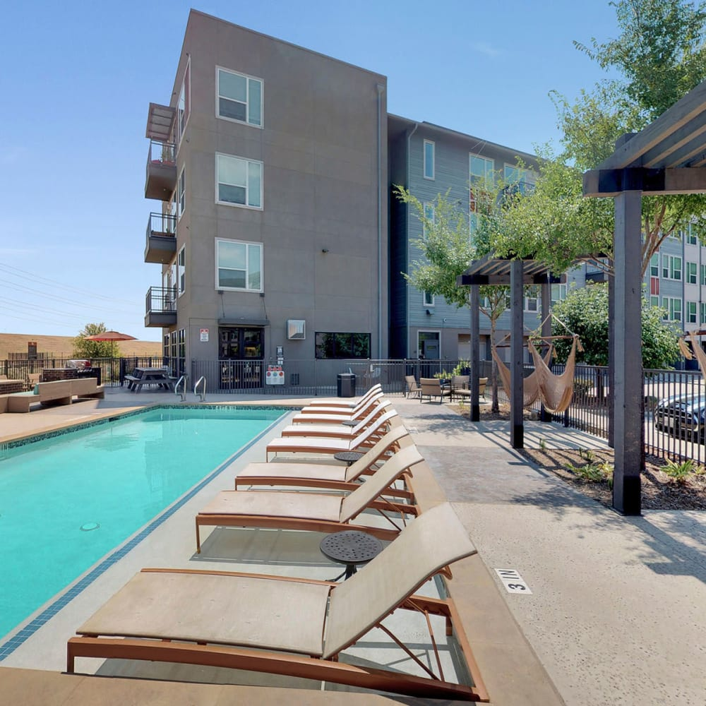 Swimming pool flanked by lounge chairs and hammocks at Oaks Trinity in Dallas, Texas
