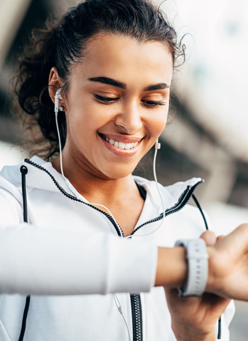 Resident setting her smart watch while exercising in Richardson, Texas near Marquis at Waterview