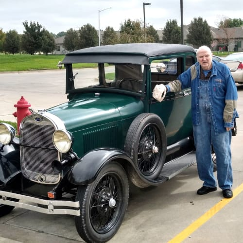 A Resident standing outside by an oldschool car at Glen Carr House Memory Care in Derby, Kansas