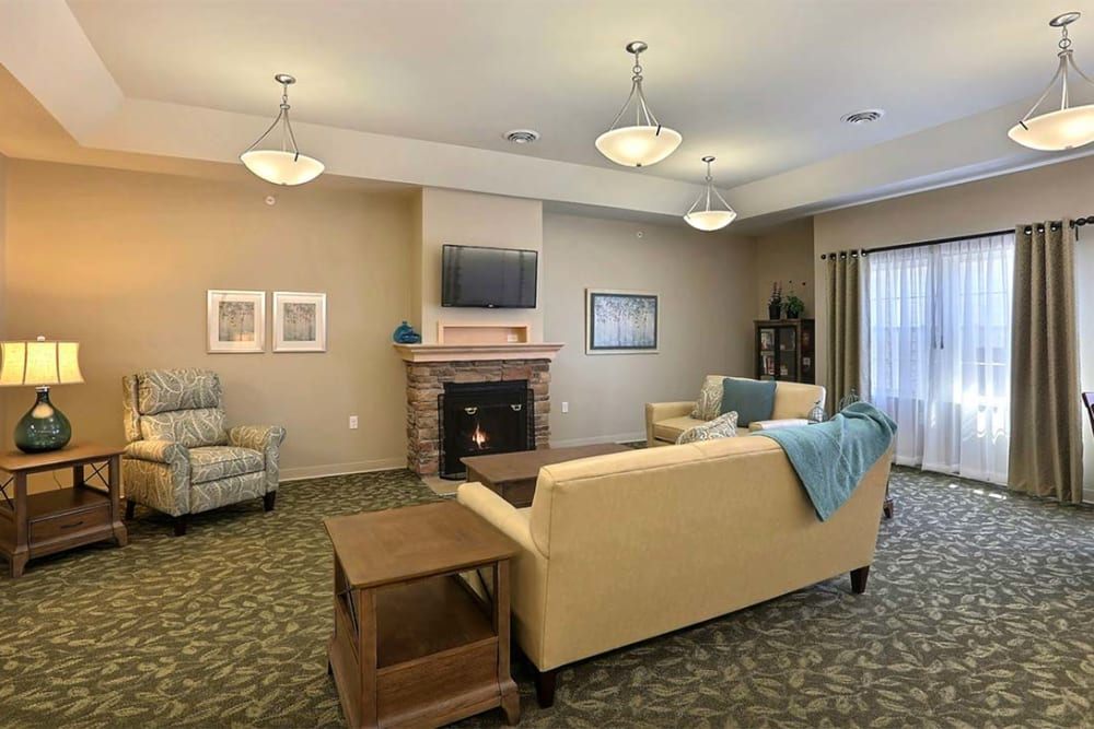 Community room with large windows and cozy seating at Milestone Senior Living in Stoughton, Wisconsin.