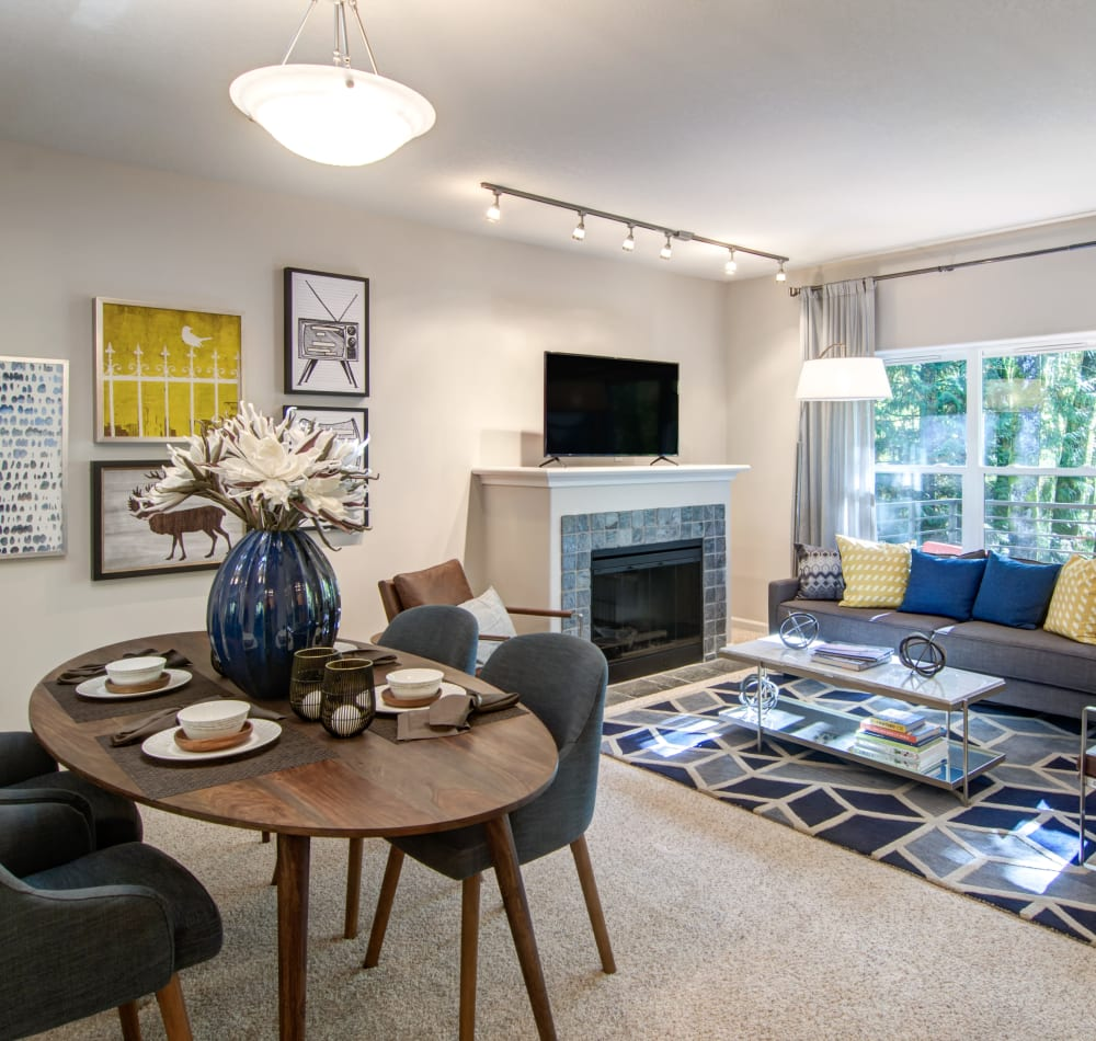 Open-concept living area with plush carpeting and a fireplace in a model home at Sofi at Forest Heights in Portland, Oregon