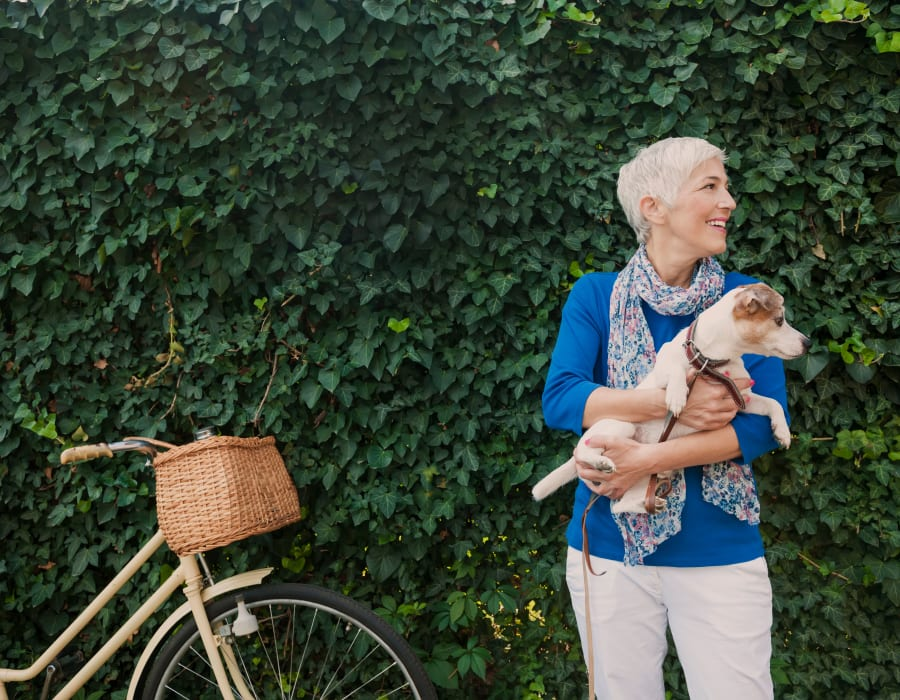 Resident standing in front of a hedge with their dog at a Radiant Senior Living community