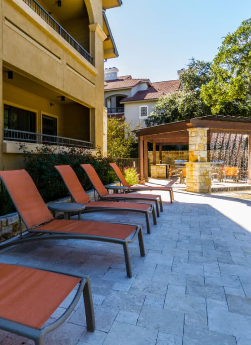 Lounge chairs lined up next to pool at Marquis at Barton Trails in Austin,