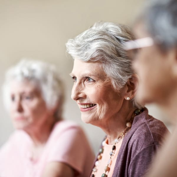 A resident listening to a talk at Pacifica Senior Living Menifee in Sun City, California.