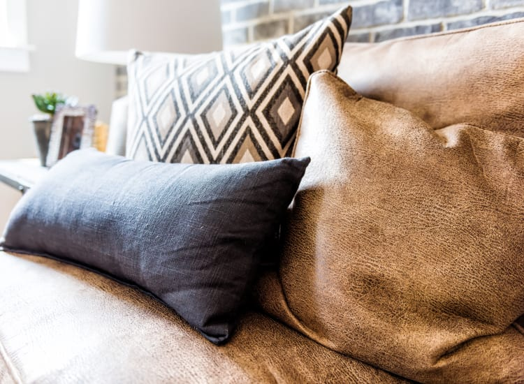 Leather couch with accent pillows in the living room of an apartment at Springs at Cobblestone Lake in Apple Valley, Minnesota