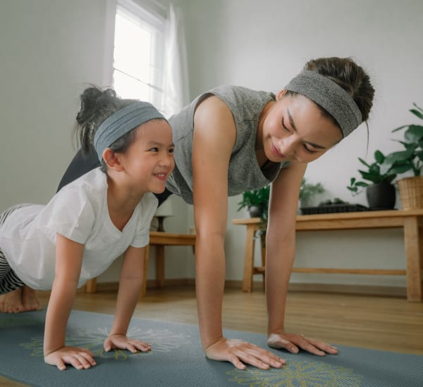 Resident doing yoga with her child at Gull Harbor Apartments in New London, Connecticut