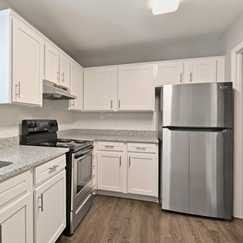 Bright white cabinetry and stainless-steel appliances in a model apartment's kitchen at Crest at Riverside in Roswell, Georgia