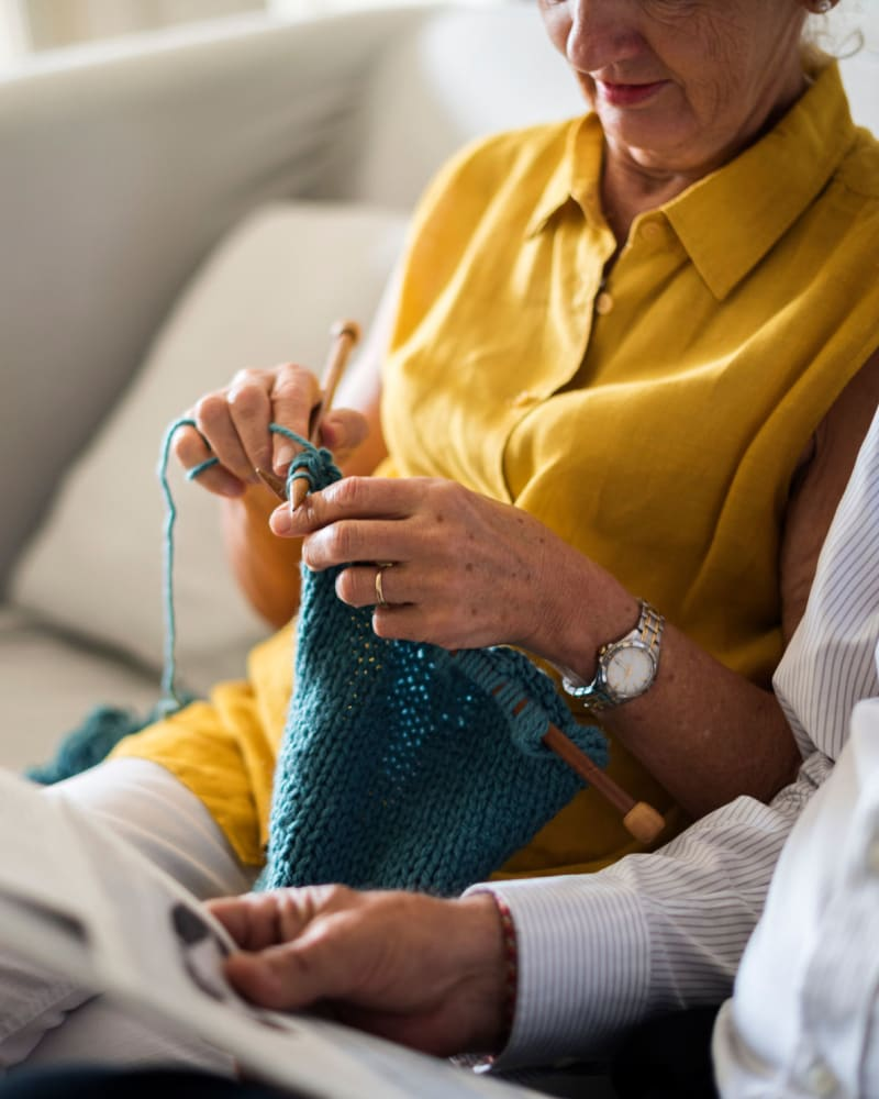 Resident knitting on the couch at Randall Residence of Centerville in Centerville, Ohio