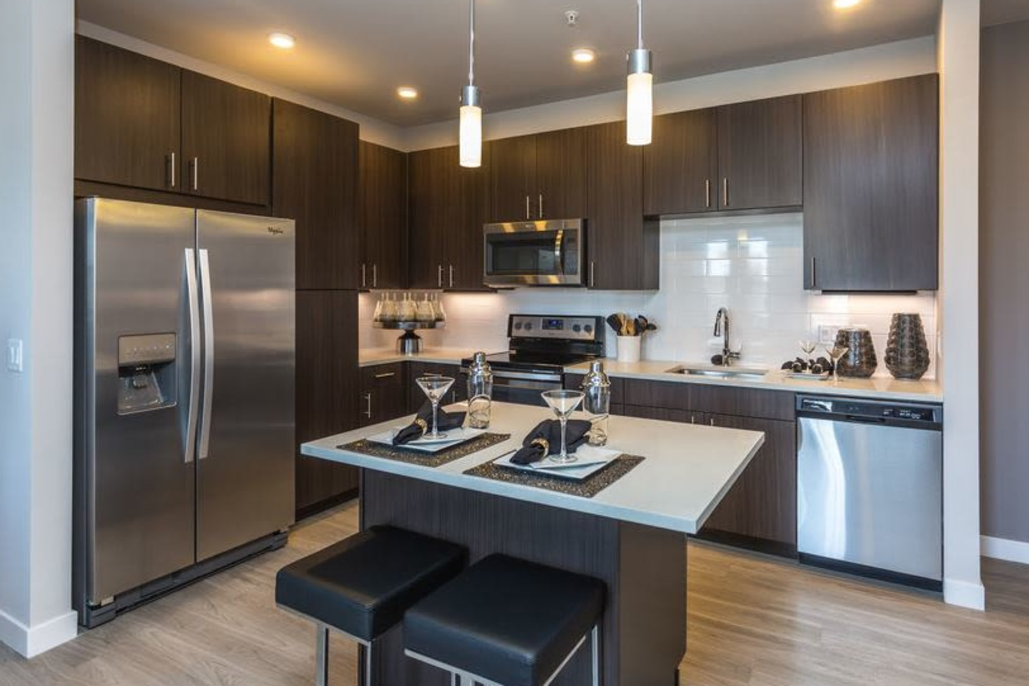Modern kitchen with stainless appliances and dark wood cabinetry at Strata Apartments in Denver, Colorado