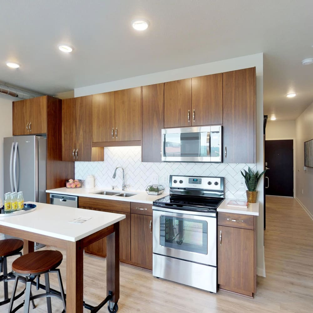 Stainless-steel appliances and custom wood cabinetry in a model home's kitchen at Oaks Union Depot in St. Paul, Minnesota