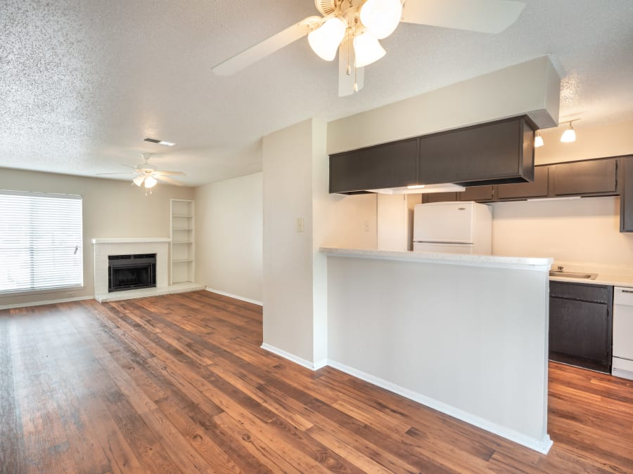 Beautiful hardwood floors in the kitchen and fireplace in the living area of a model home at The Madison in Dallas, Texas