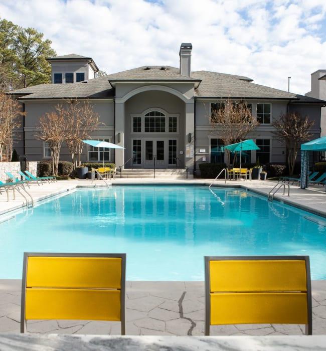 Chairs surrounding the sparkling community pool at Marq Perimeter in Atlanta, Georgia