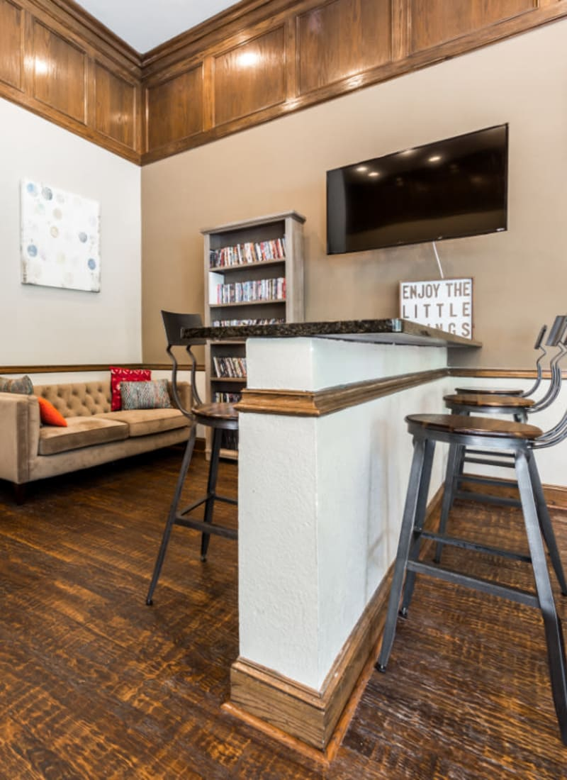 Community clubhouse game room with couch and island counter with stools at Marquis at Waterview in Richardson, Texas