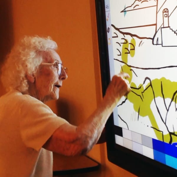 Resident drawing on a large touchscreen at Quail Park Memory Care Residences of West Seattle in Seattle, Washington