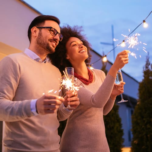 Resident couple with sparklers at twilight on the private balcony outside their home at Reserve at Peachtree Corners in Norcross, Georgia