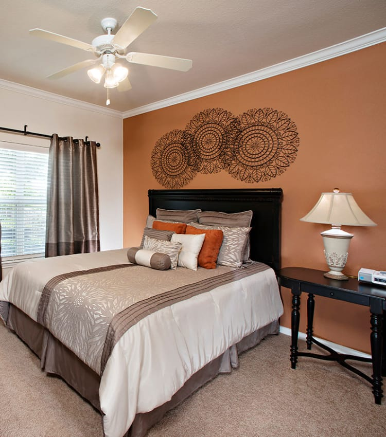 Model bedroom with a ceiling fan at Estancia at Ridgeview Ranch