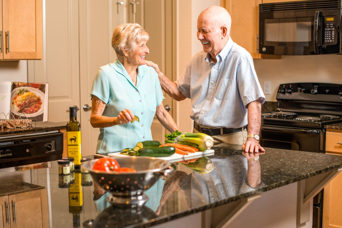 A couple standing in their kitchen smiling at Watercrest at Kingwood in Kingwood, Texas