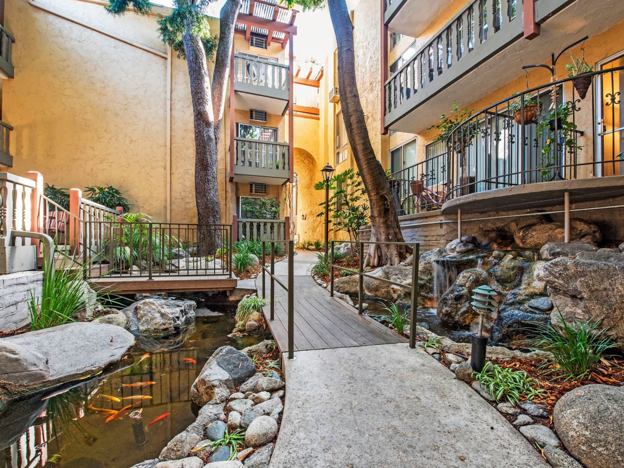 Walkway over a koi pond and with a small waterfall at Mediterranean Village in West Hollywood, California