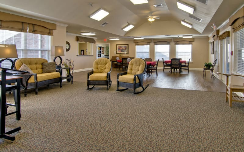 Community areas with rocking chairs and dining tables at Etheridge House Senior Living in Union City, Tennessee