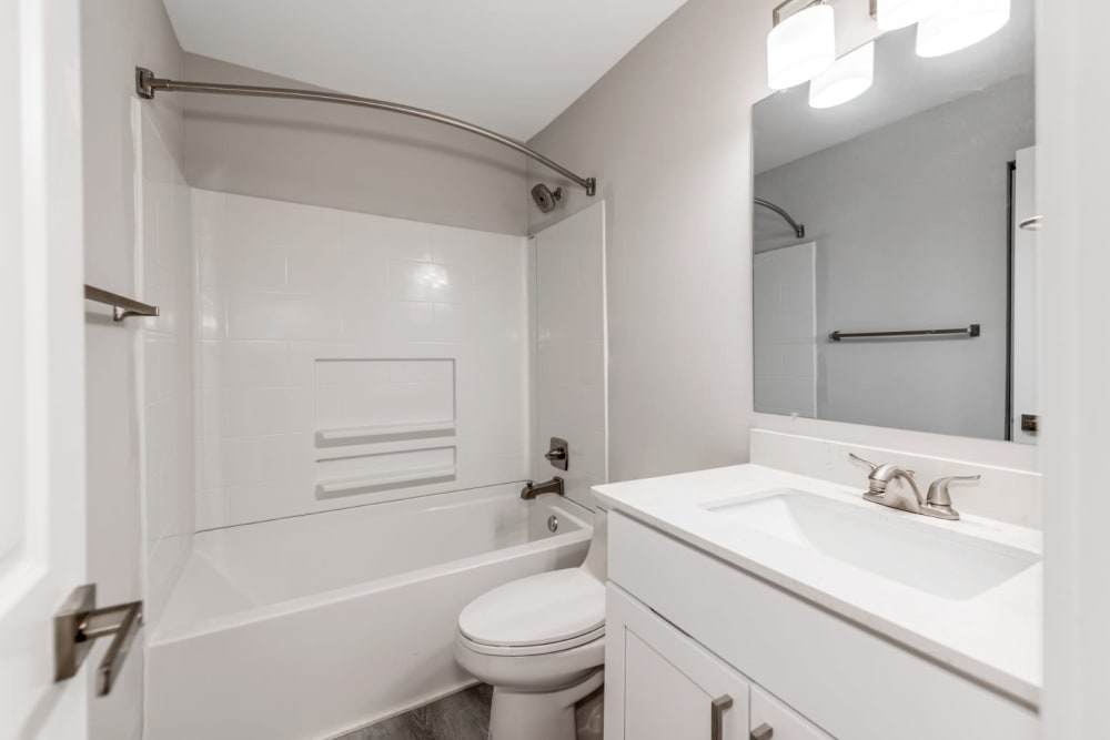 Bright bathroom with large mirror at The Flats at Arrowood in Charlotte, North Carolina