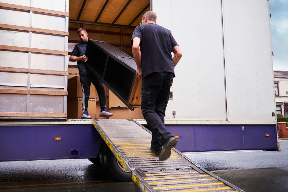 Two men loading furniture into a moving truck near A-American Self Storage in Los Angeles, California