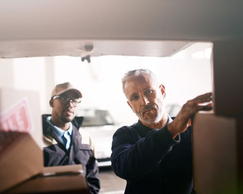 Two men unloading a van at an A+ Storage location