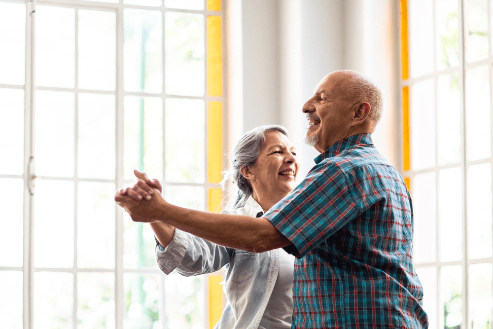 Two residents dancing in a brightly lit lounge at Hanover Place in Tinley Park, Illinois
