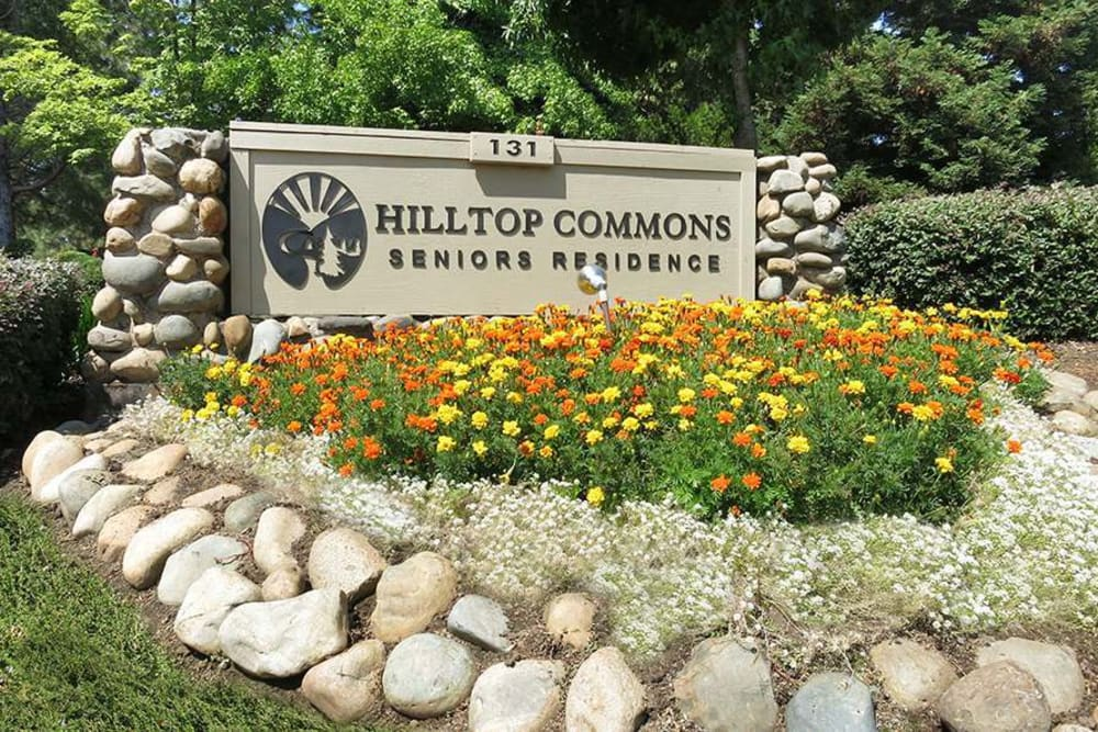 Exterior sign with flowers surrounding at Hilltop Commons Senior Living in Grass Valley, California