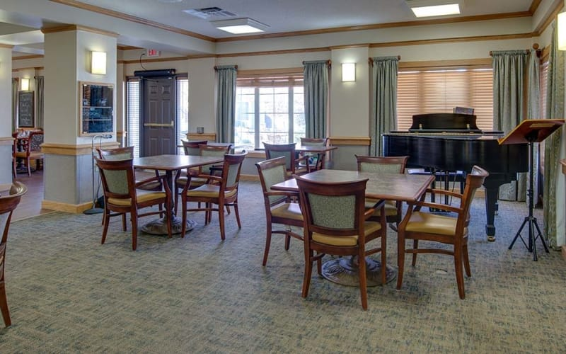 Indoor lounge with a piano at Waldron Place Senior Living in Hutchinson, Kansas