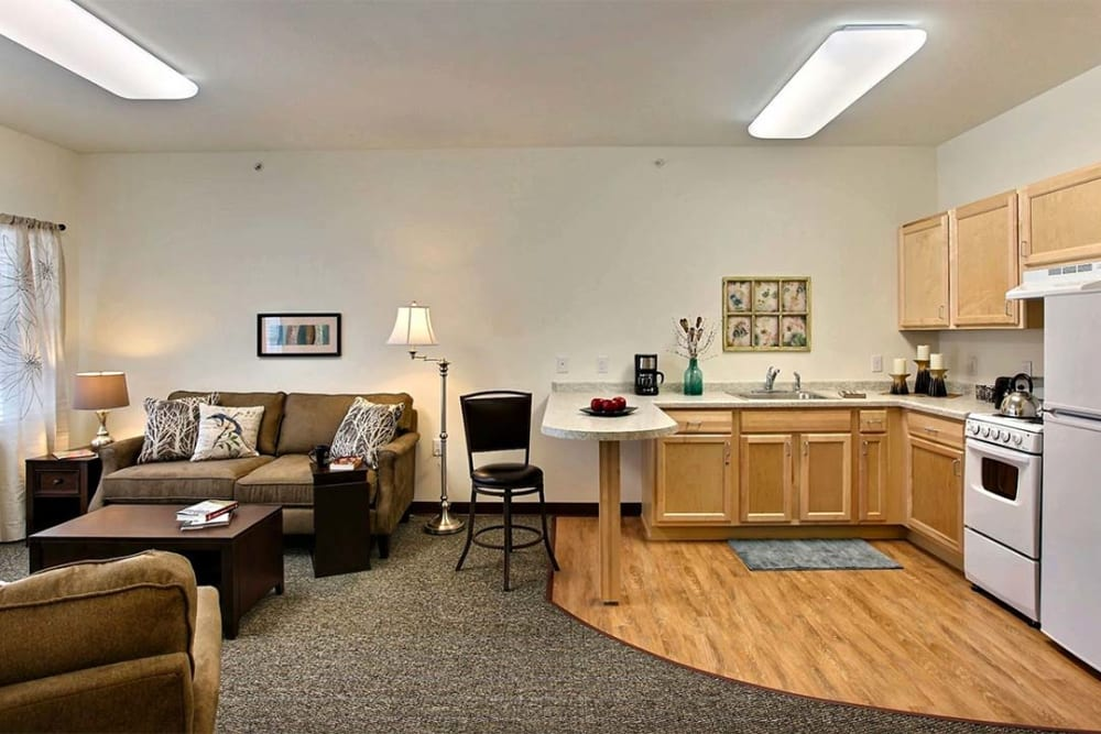 Apartment with living room and full kitchen at Milestone Senior Living in Woodruff, Wisconsin.