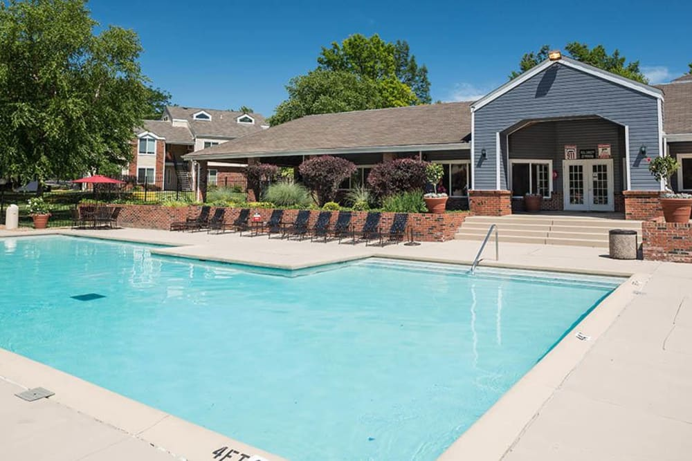 A swimming pool with a spacious sundeck for lounging at Sunbrook Apartments in Saint Charles, Missouri