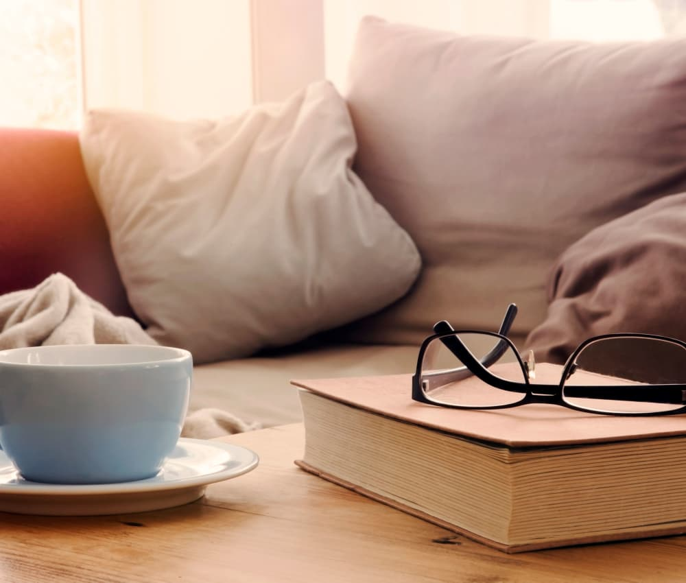 Reading glasses and book on coffee table at Ardendale Apartments in Sacramento, CA