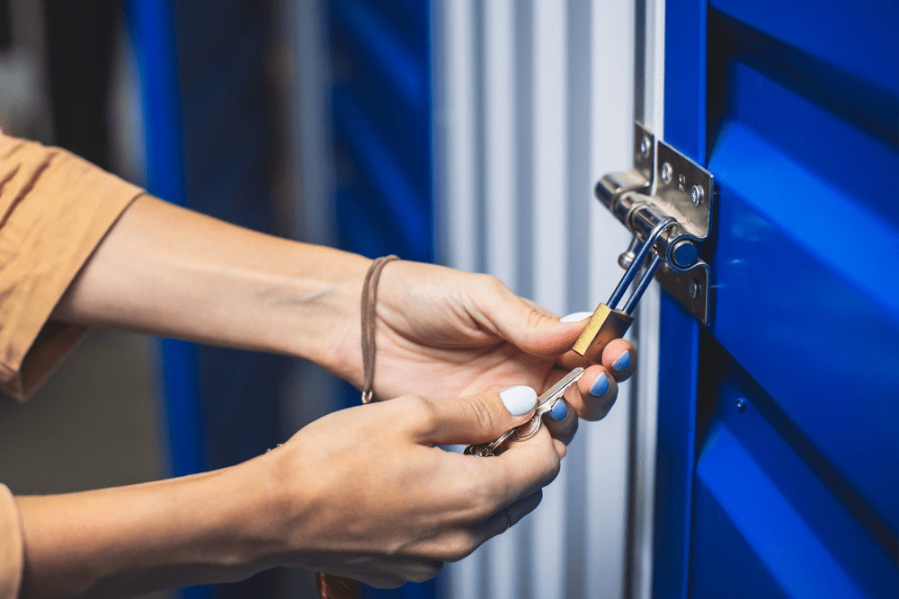 Closing the padlock on a blue storage unit door at 21st Century Storage in Long Island City, New York