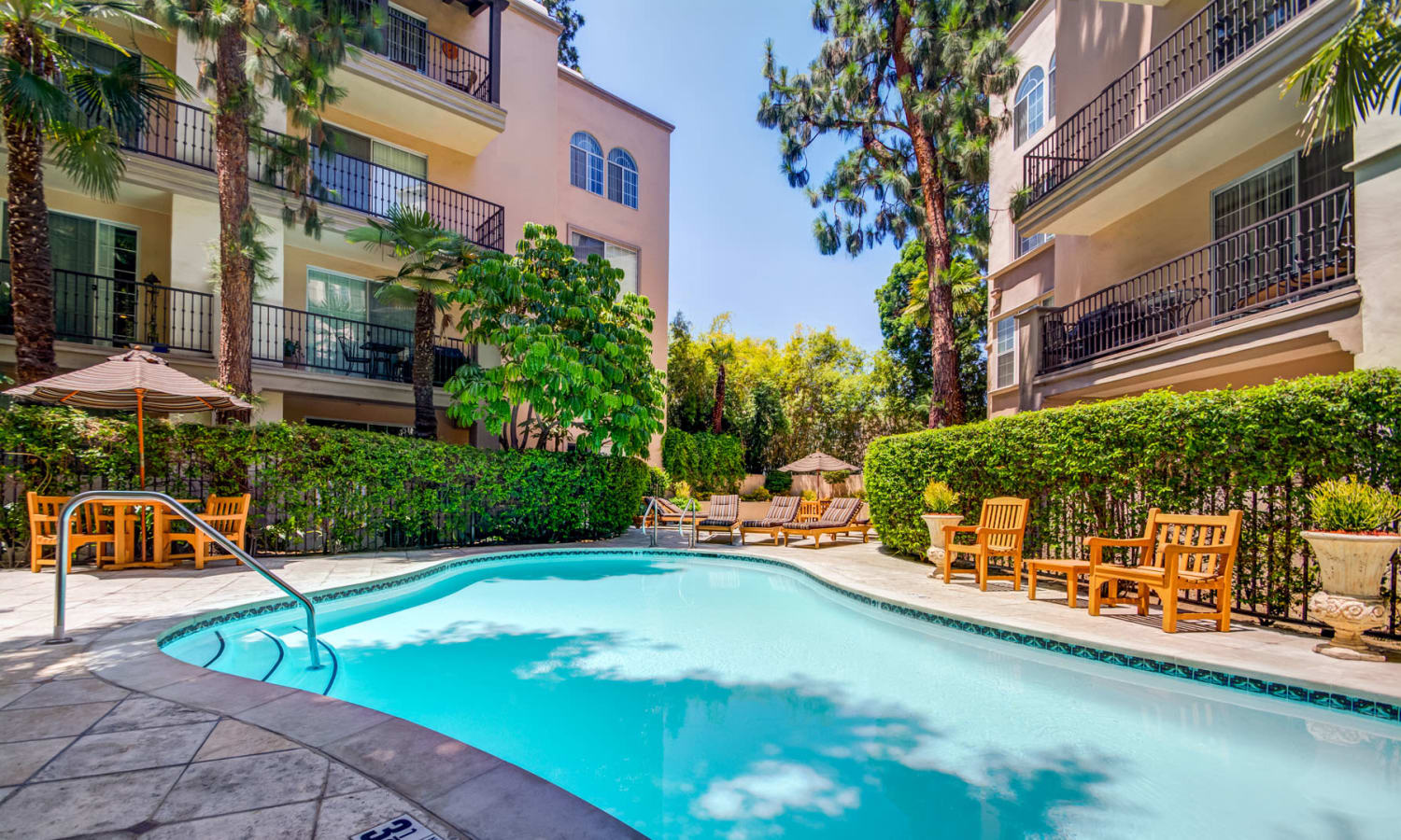 Resort-style swimming pool on a beautiful day at L'Estancia in Studio City, California
