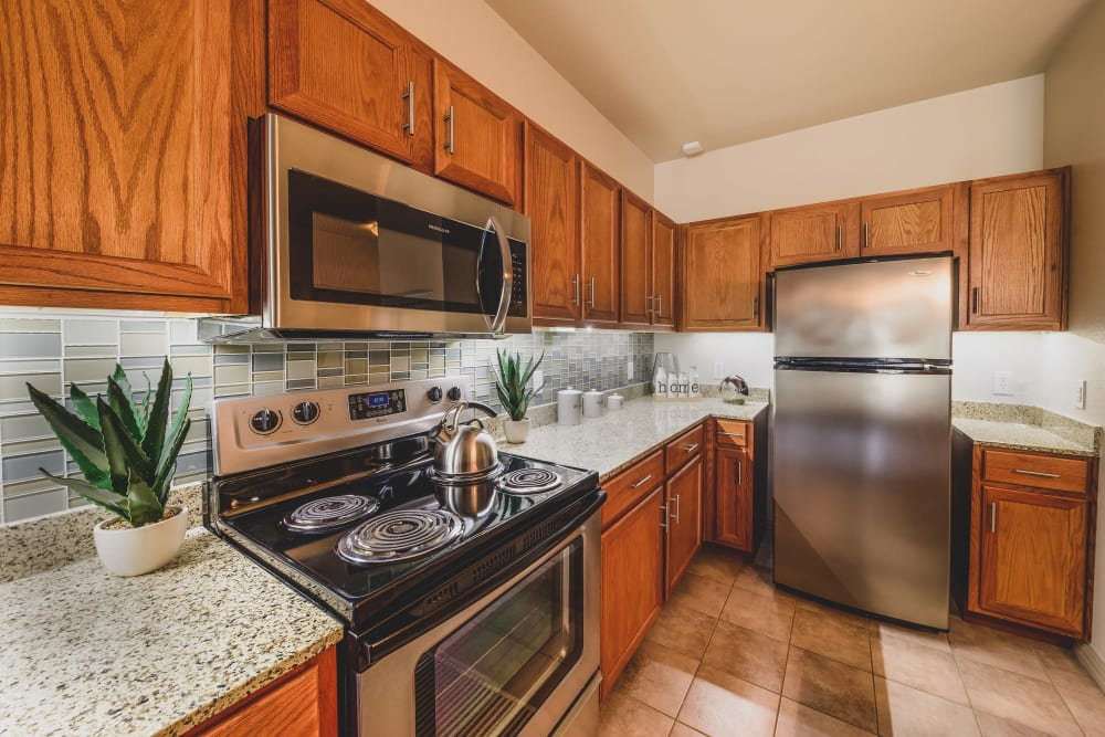 Kitchen with wood cabinets and granite countertops at Evolv in Mansfield, Texas
