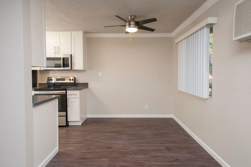 Spacious room with hardwood floors and a ceiling fan at Regency Plaza Apartment Homes in Martinez, California