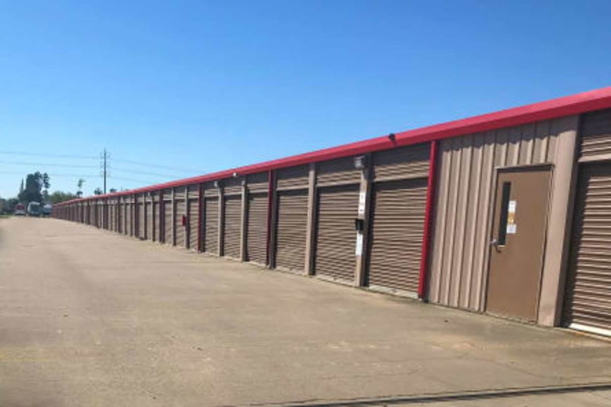 Outdoor drive-up units with brown doors at Storage Star Tomball in Tomball, Texas